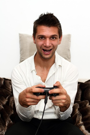 Smiling Gamer sitting on couch with controller and playing photo