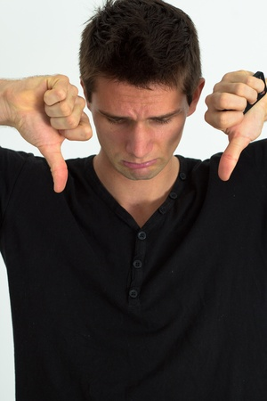 Sad man looking down in pain fully stressed and doing thumbs down photo