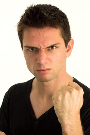 enojo: Hombre joven que muestra el pu�o y mirando muy agresivo