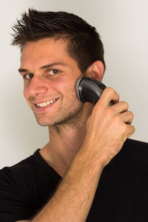 electric razor: Man shaving face with electric razor