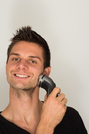 Man shaving face with electric razor photo