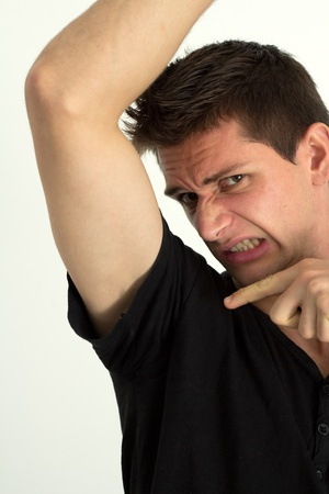 armpit hair: Man smelling bady under hes armpits and pointing there with his finger Stock Photo