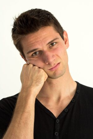 Worried young man with hand on face photo