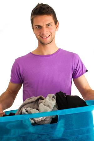 lavadora con ropa: Hombre joven que hace el lavado y sonriente