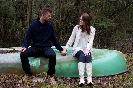 green boat: A cute young couple sitting on a old boat and holding hands