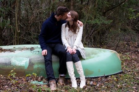 A cute young couple sitting on a old boat and kissing Stock Photo