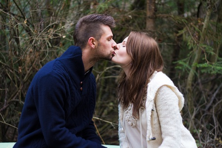 Young couple kissing in the forest in front of trees photo