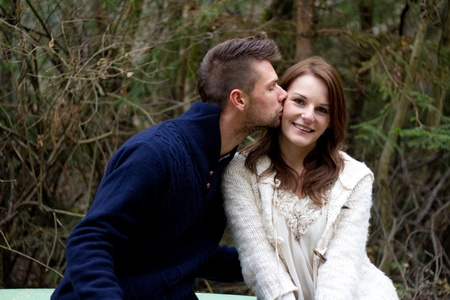 Man kissing woman on the cheek in the forest in front of trees