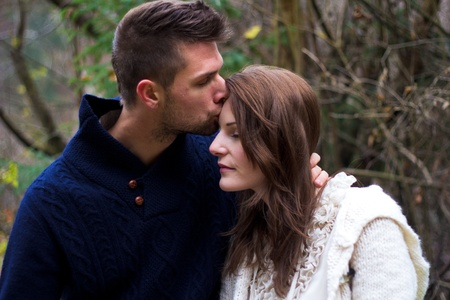 Man kissing woman on the cheek in the forest in front of trees photo