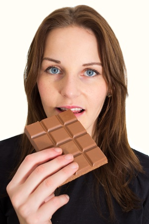 Young Brunette Woman Eating A Milk Chocolate Bar photo