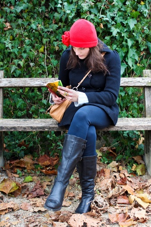 clothed: Woman Sitting On A Bench And Reading A Book, clothed in warm winter clothing Stock Photo