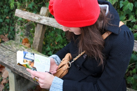 Woman Sitting On A Bench And Reading A Book, clothed in warm winter clothing photo