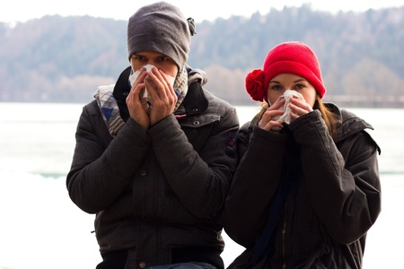 A Young Couple Next To Each Other Blowing Their Noses And Looking at the camera Stock Photo