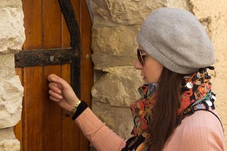 Les jeunes femmes Brunette avec des lunettes qui frappent à une porte en bois Taken From Close-Up Éditoriale