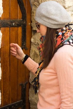 tocar la puerta: Mujeres Jóvenes Morena Con gafas de sol llamando a una puerta vieja de madera Tomado de Close-Up Editorial