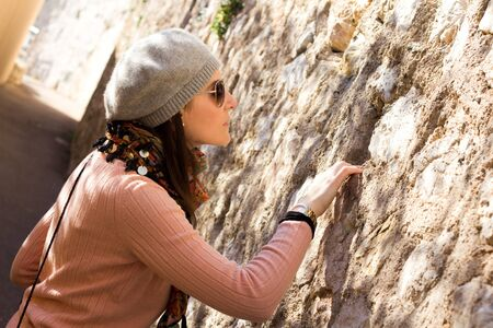 Interested Woman Looking Into A Hole In A Stone Wall photo