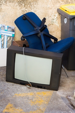 Old television lying on the floor next to the bin photo
