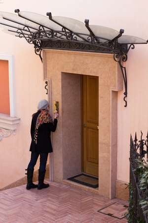 show ring: Woman Ringing The Entrance Door To A Modern Luxurious Flat Stock Photo