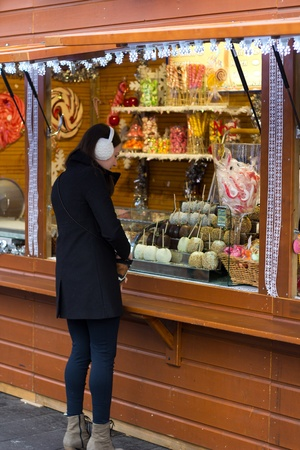earmuffs: Young Brunette Woman Buying Candy At A Kiosk Stock Photo