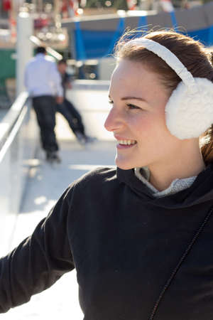 earmuffs: Young Brunette Woman With Earflaps Smiling While On The Ice Rink