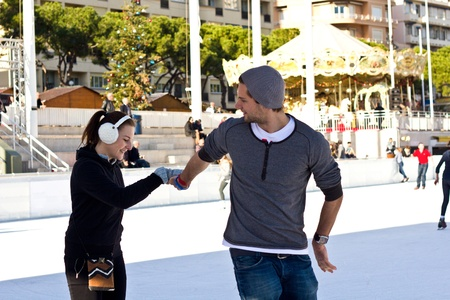 Young Couple Ice Skating Together And Having Fun Doing A Figure photo