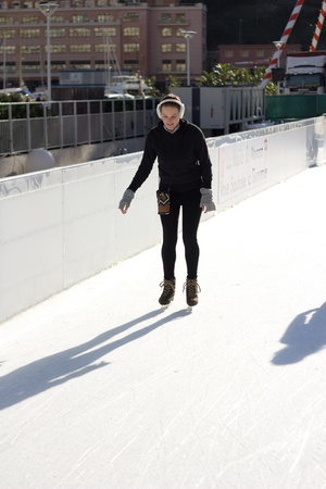 Slim Young Woman Ice Skating On An Ice Rink photo