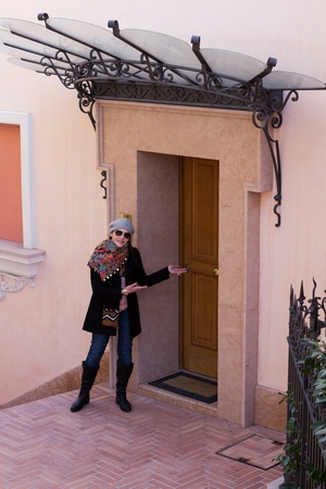 Woman Showing The Entrance Door To A Modern Luxurious Flat photo
