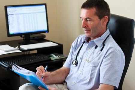 Doctor schrijven op een document in de praktijk Hij