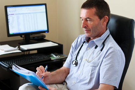 practitioner: Doctor Writing On A Document In Hes Practice