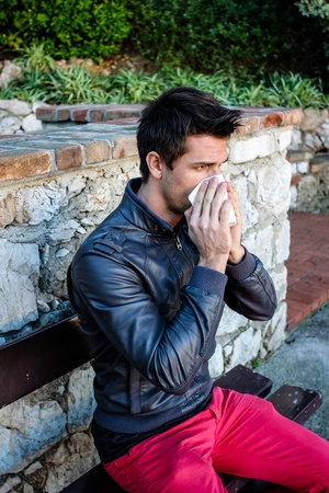 Attractive Brunette Man With Red Pants Blowing He's Nose While Sitting On A Bench In A Park Stock Photo - 13108372