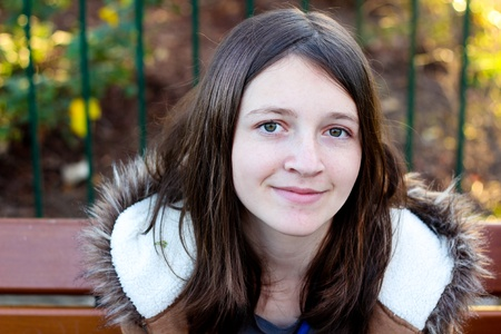 naturally: Portrait Of A Young Brunette Girl Smiling While Sitting Outside On A Bench