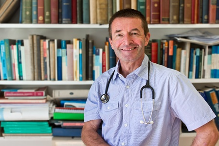 White Doctor In Front Of A Book Shelf Full Of Medical Books