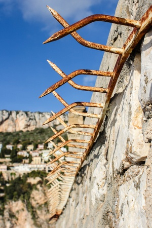 A Peaky Fence On A Wall With Bright Vibrant Blue Sky In The Background Stock Photo