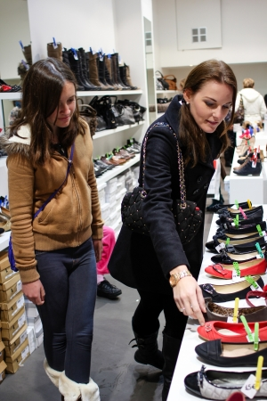 Two young brunette women shopping for shoes in a small boutique