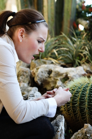 Woman hurt herself on a thorn from a cactur and is holding her hand