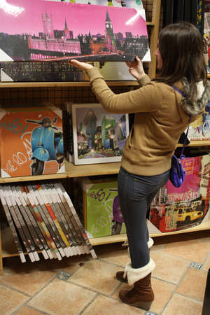 Woman in a store looking at big prints of pictures