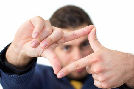 Brunette man looking through he's fingers Stock Photo - 13901924