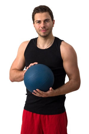 Attractive brunette man in a black tank top and red pants working out with a medicine ball Stock Photo - 13901956