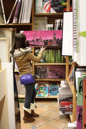 Woman in a store looking at big prints of pictures photo