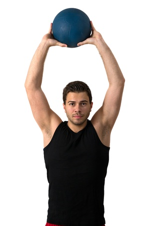 Attractive brunette man in a black tank top and red pants working out with a medicine ball photo
