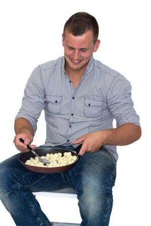 Young Attractive Man Cooking gnocchi in A Pan photo