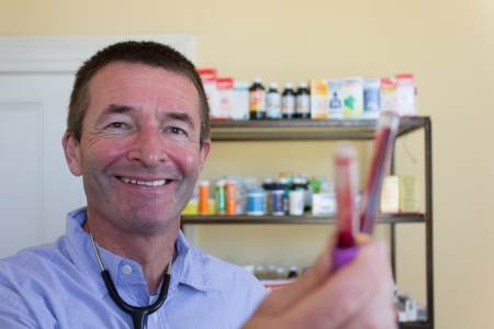 General Practicioner Showing blood capsules and smiling Stock Photo - 14748984