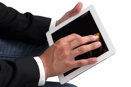 A Man with blue jeans working on a tablet pc with he's hand Stock Photo - 14749595