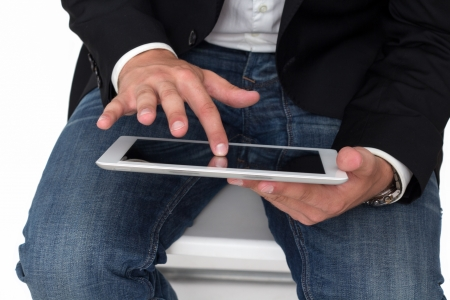 A Man with blue jeans working on a tablet pc with he's hand Stock Photo - 14749633