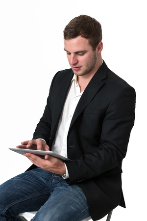 Young Businessman in jeans working on a tablet pc Stock Photo - 14749640