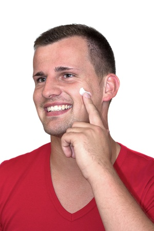Young white man with moisturizer cream in his face in front of isolated background photo
