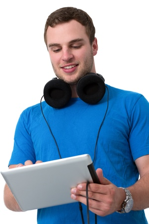 Young man with headphones and blue t-shirt working on a tablet pc Stock Photo - 14750961
