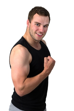Young attractive man flexing his biceps and smiling Stock Photo - 14750907