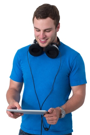 Young man with headphones and blue t-shirt working on a tablet pc Stock Photo - 14802711