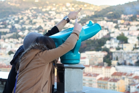 Boy and Girl looking through a turquoise telescope and pointing somewhere photo